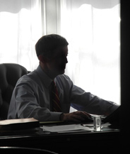 Walter McKee sits at his desk in silhouette